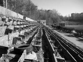 Руины стадиона Арсенал. Так трибуны выглядели  в 90-е годы.  Скамейки уже разобрали, но стадион еще не зарос деревьями. Нет ещё и тонн пластикового мусора. <br><i>Прим. ред. Ліски (коментар) Это не 90-е. Это фото я снял в 2004-м. Николай</i>.